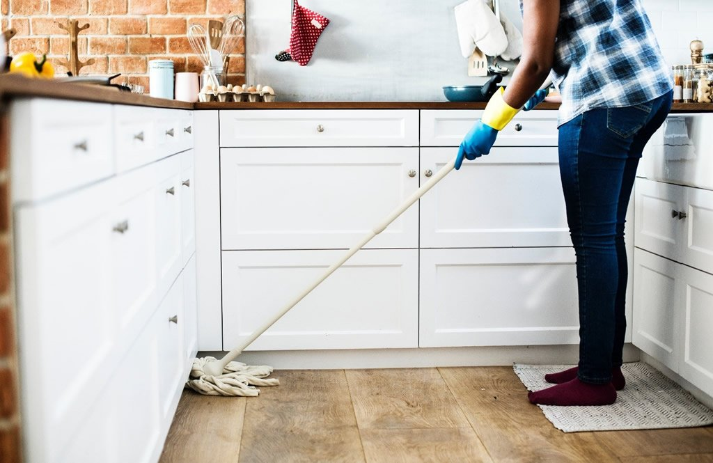 person mopping kitchen for spring cleaning