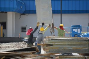 Three workers on a construction site handling building materials